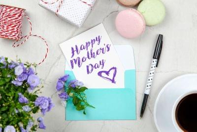 Canva%20 %20happy%20mothers%20day%20card%20beside%20pen,%20macaroons,%20flowers,%20and%20box%20near%20coffee%20cup%20with%20saucer2