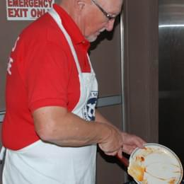 Exchange club member in red shirt cleans plate
